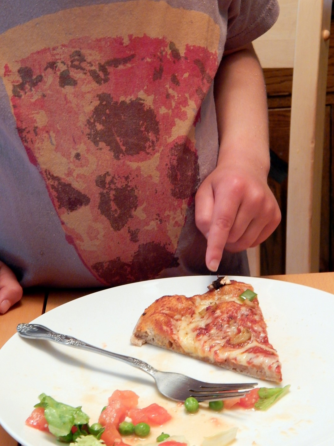 Child pointing to a slice of pizza
