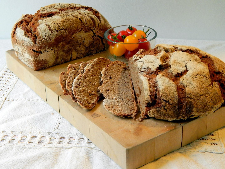 Sliced loaf of dark sourdough rye.