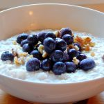 Bowl of oatmeal with blueberries and walnuts.
