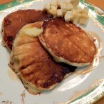 Three buttermilk pancakes with chopped banana and syrup.