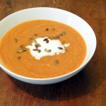 Bowl of curried pumpkin soup with coconut cream.