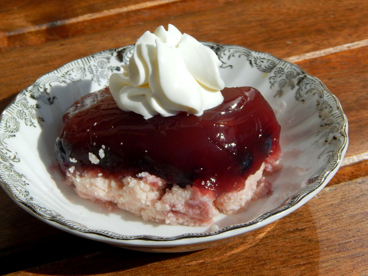 Bowl of layered jello with whipping cream.
