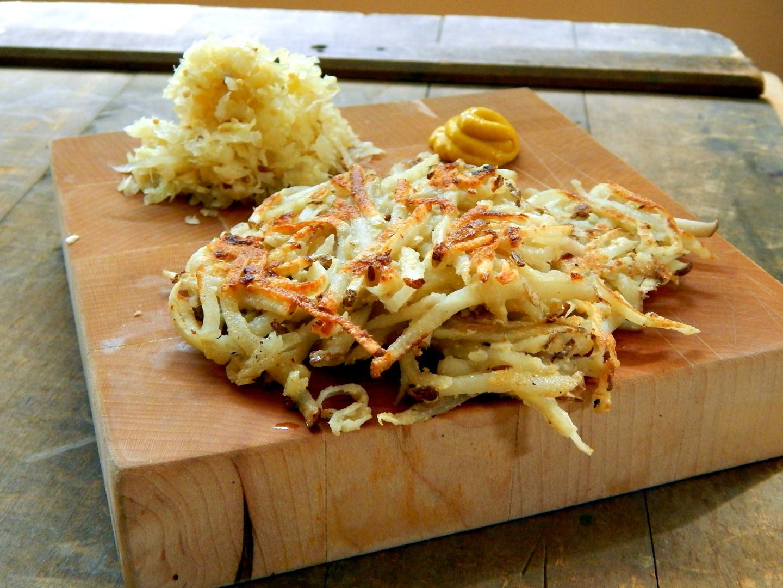 Wooden board with sauerkraut latkas and mustard