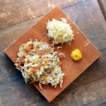 Wooden board with sauerkraut latkas and mustard