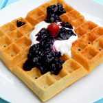 Buttermilk waffle with whipping cream, cherry sauce and a strawberry