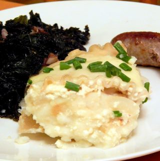Pierogi casserole on plate with sausage and kale.