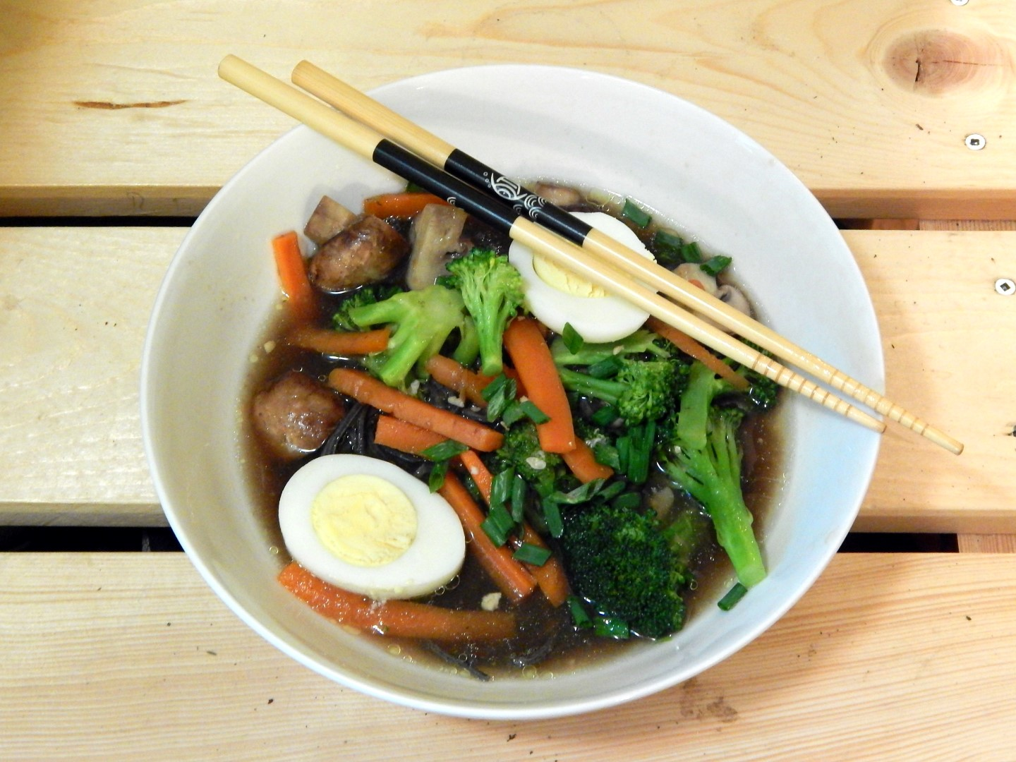 Miso soup broth with eggs and vegetables.