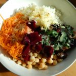 Bowl with chickpeas, greens, sauerkraut, carrots, and beets.