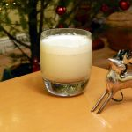 Whiskey glass of eggnog in front of a christmas tree.