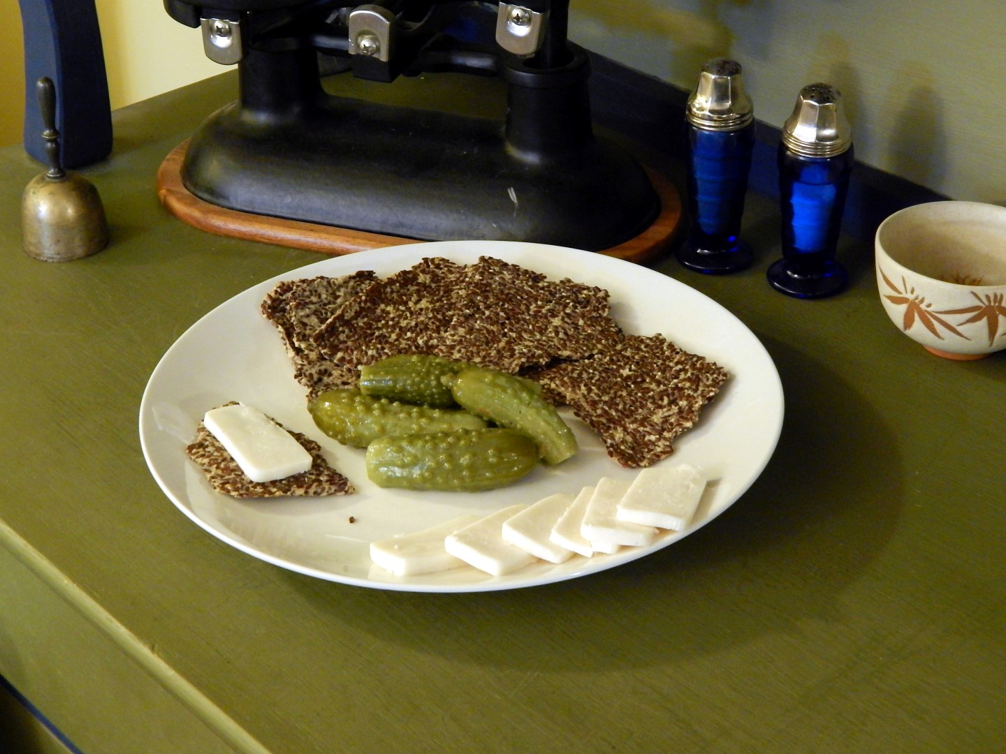 Plate with seedy crackers, pickles and cheese.