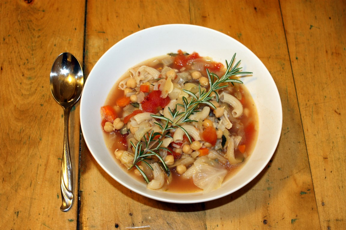 Top-down view of minestrone soup with sprig of rosemary.