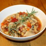 Bowl of minestrone soup with rosemary sprig.