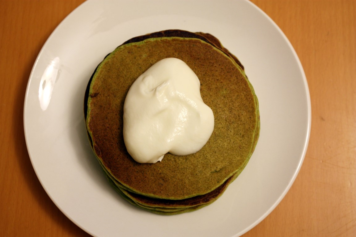 Stack of pancakes topped with sour cream.