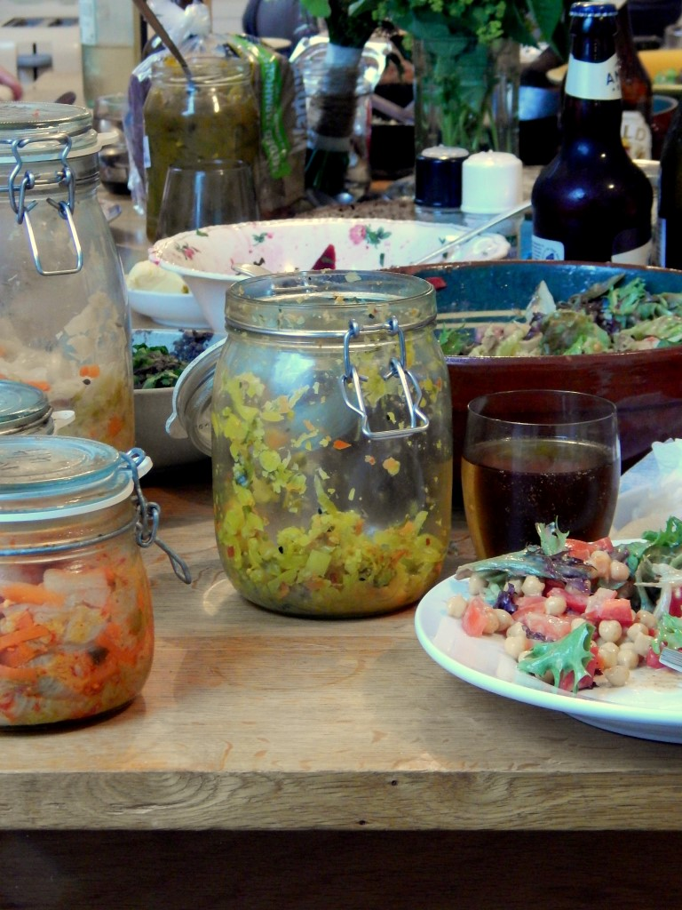 Table with mixed jars of fermented vegetables, including piccalilli