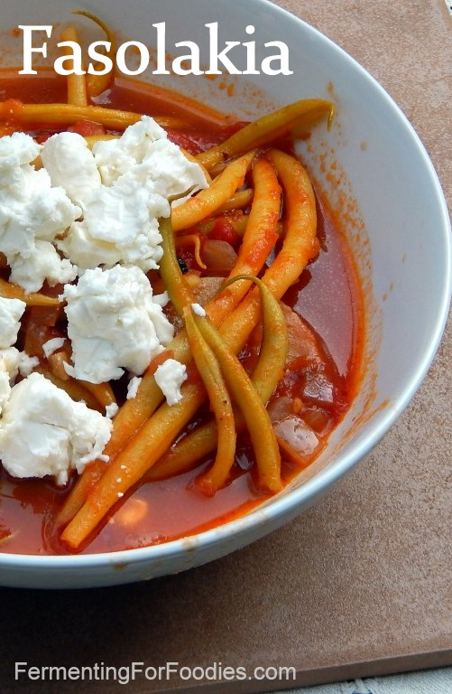 Bowl of green beans stewed with tomatoes topped with feta.