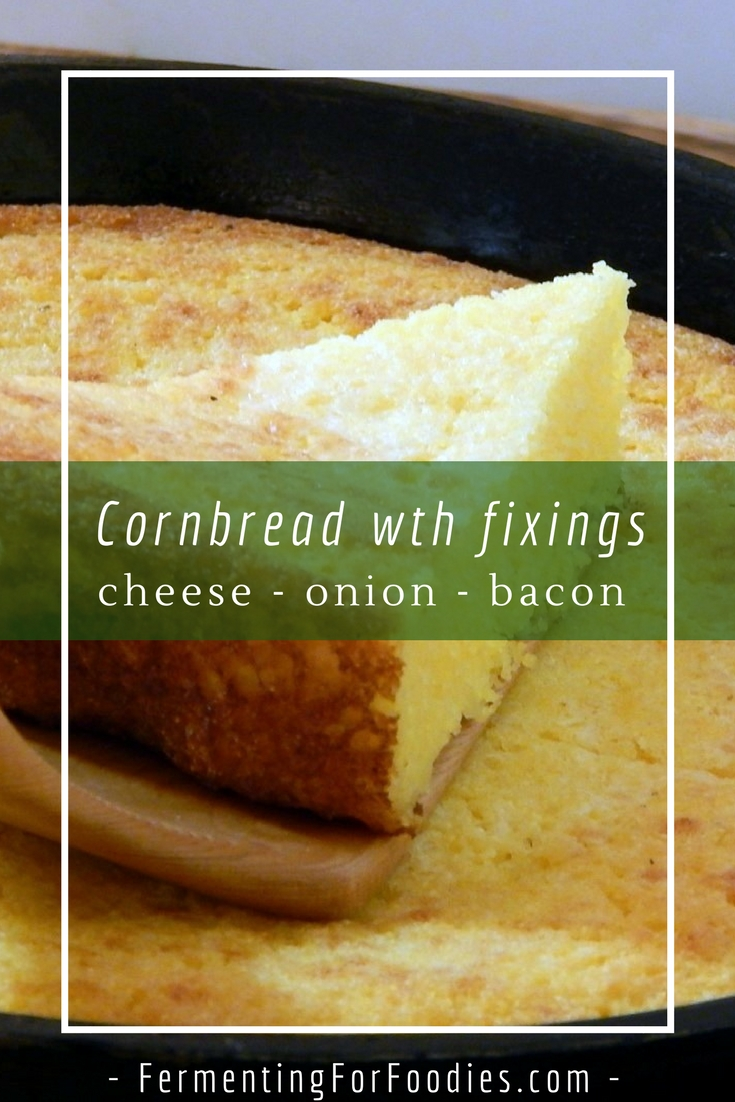 Southern style cornbread in a cast iron pan with fixings: cheese, onion, bacon, cracklings, sun-dried tomato, chipotle peppers