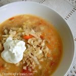 Comforting and cosy sauerkraut soup with sausage, tomatoes and potatoes